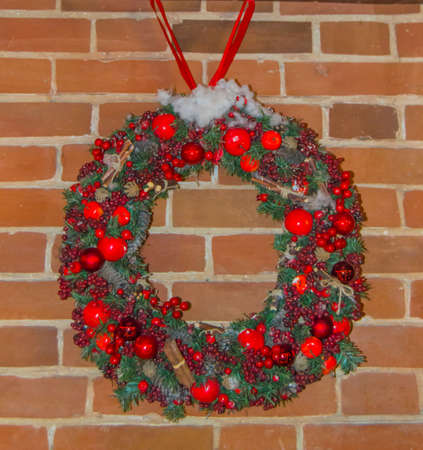 The red brick wall of the house is decorated for Christmas. Christmas tree with garlands and Christmas holiday wreath for home decoration, outdoor. Фото со стока