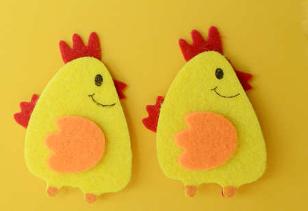 Two cute yellow felt chickens on yellow Banco de Imagens