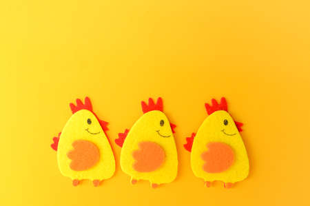 Three cute yellow felt chickens in a row, handmade, diy, kids Easter crafts, copy space, funny handmade idea