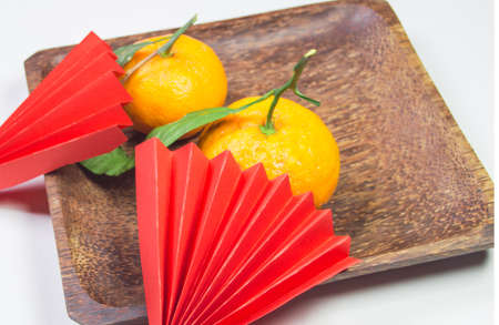 Chinese New Year, composition with mandarins, paper red origami fans on a dark wooden plate on a white background