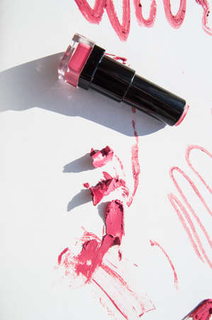 Black used tube of lipstick on a white background, various smudged lines and textures of pink, red lipstick, bright sunlight and shadows, beauty concept. 免版税图像