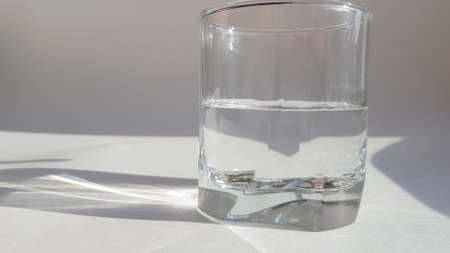 Glass transparent glass with clear water on gray background