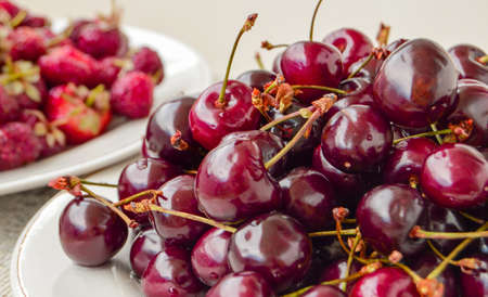 Lots of ripe juicy cherries in a white bowl, summer berry harvest, food background Stok Fotoğraf