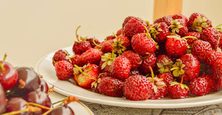 Lots of ripe juicy strawberries in a white bowl, summer berry harvest, food background