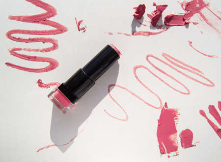 Black used tube of lipstick on a white background, various smudged lines and textures of pink, red lipstick, bright sunlight and shadows, beauty concept