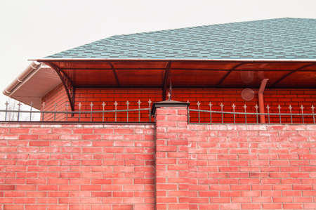 The fence wall is made of red brick, the roof of the house is visible from behind the fence. modern cottage construction