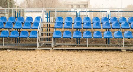 Blue seats on an empty grandstand in an outdoor beach volleyball stadium