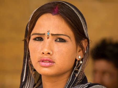 agrees: Bikaner, Rajasthan, India - 17 August 2012: this young Indian girl with sad eyes agrees to be photographed by tourists Editorial