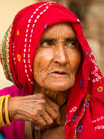 observes: Mandawa, Rajasthan, India-August 15, 2012: elderly Indian woman carefully observes a group of tourists from Europe, strolling through the city
