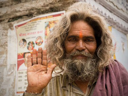 sadhu: Pushkar, Rajasthan, India - 20 August 2012: Portrait of an Indian Sadhu who greets me with the typical gesture of the hand raised Editorial