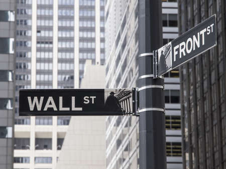 Wall St  street sign with tall buildings in the background photo