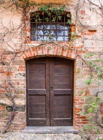 saluzzo: Facade of red brick retro style house with black wooden gate at entrance in Italy.