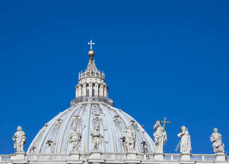 colonade: Close-up shot of the Colonade of St. Peters Square in Vatican City with the dome of St. Peters in the background. Stock Photo