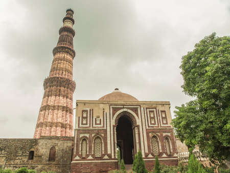 adjacent: Qutub Minar, famous minaret in India with an adjacent mosque Stock Photo