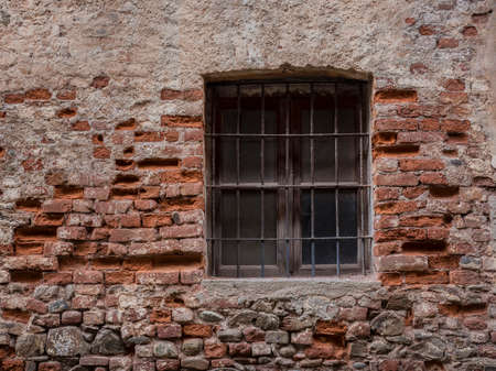 saluzzo: Old window with grate in the center of the historical Saluzzo