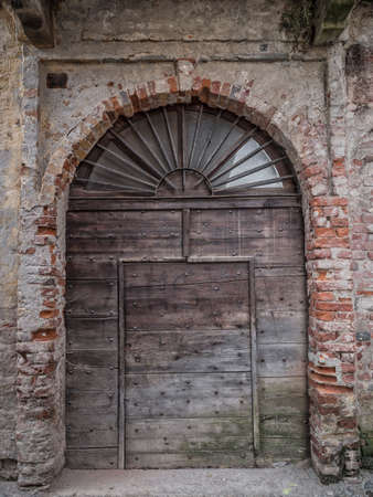 saluzzo: old wooden door of an abandoned house in the historic center of Saluzzo Stock Photo