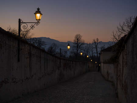 saluzzo: Saluzzo, lighting of a typical street of the old town at sunset Stock Photo