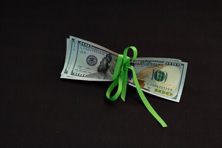 Four banknotes four hundred us dollars on a black background tied with a green ribbon