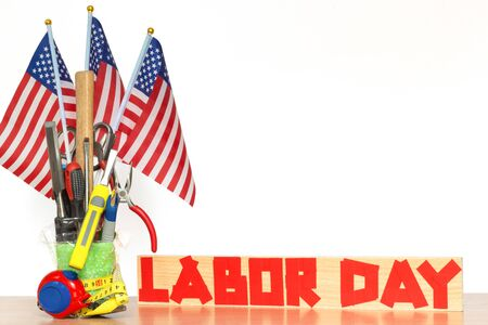 Bouquet of tools with US flags on a table and duct tape text on a board, concept of the patriotic holiday of labor day