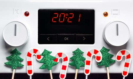 Numbers 2021 on digital display of electric stove with Christmas decorations, festive New Year concept for holiday restaurant or home cooking