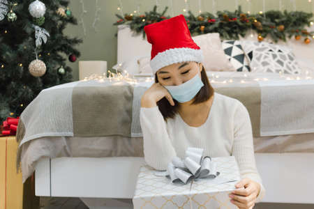 Young asian sad lonely woman in face mask and santa hat sits by the bed with gift, quarantine or self isolation at New Year holiday or christmas time