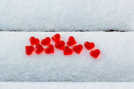 Bright red glass hearts on snowy bench at cold winter, love symbol, Valentines Day holiday concept