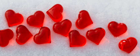 Bright red glass hearts on powdery snow at winter day, love symbol, Valentines Day holiday concept