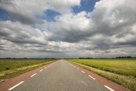 Route en Hollande avec piste cyclable rouge des deux côtés, perspective, sous un ciel nuageux menaçant et sombre et entre des prairies vertes et un horizon lointain et droit.