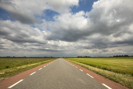 Strada in Olanda con pista ciclabile rossa su entrambi i lati, prospettiva, sotto cieli nuvolosi minacciosi e scuri e tra prati verdi e un lontano orizzonte rettilineo.