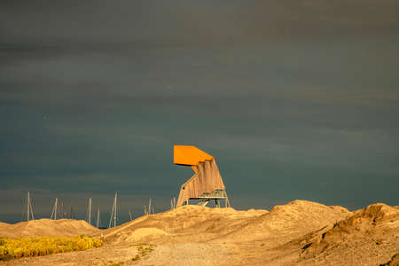 Bird watching tower in the dunes in at night sunset, located in the new land at the Marker Wadden in the Markermeer, a lake in the Netherlands. 免版税图像