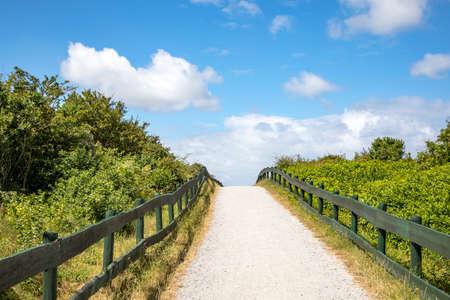 Beach transition on Schiermonnikoog, green fences to the horizon, gravel path across the dunes to the beach at schiermonnikoog island of the netherlands 免版税图像