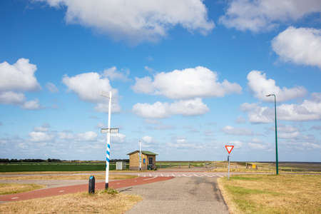 Schiermonnikoog Island, a corner in the road to the ferry, low horizon and beautiful cloudy sky