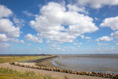 Wadden Sea at Schiermonnikoog, low tide on the coast, the ferry landing point in the distance and a beautiful skyscape all little sheep clouds