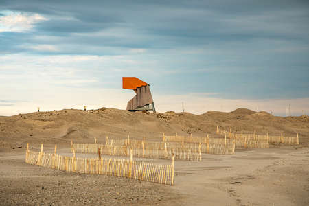 Bird watching tower and wood structure fences in the dunes in evening sunset, at the Marker Wadden in the Markermeer, in the Netherlands. 免版税图像