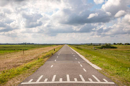 Road in Holland with white cycle path lines on both sides, perspective, under heavy threatening cloudy skies and between green meadows and a faraway straight horizon.