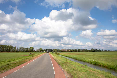 Road in Holland with red cycle path on both sides, perspective, under heavy cloudy skies and between green meadows, agricultural vehicle drives at the end of the road