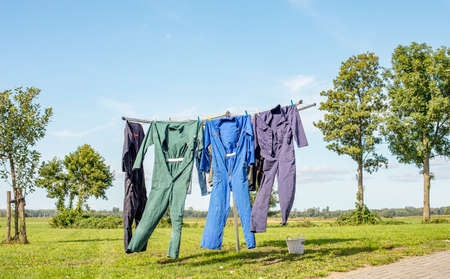 Work overalls hang to dry on the line of the laundry rack with the clothes peg basket next to it on a sunny summer day. 免版税图像
