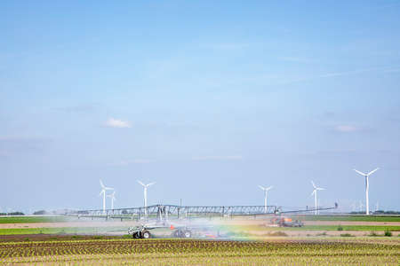 Rainbow while irrigation sprinkler is watering crops on fertile farm land in Almere, Netherlands.