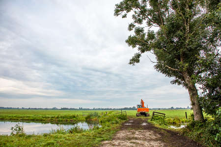 Red tractor drives through a gate next to a creek into field, agricultural transport, cultivation of fertile land or soil, with a cloudy sky background.
