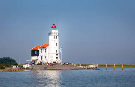 Lighthouse 'The Horse of Marken' aka as 'The horse of Marken' with a lot of rubbish around it seen from the Markermeer. 免版税图像