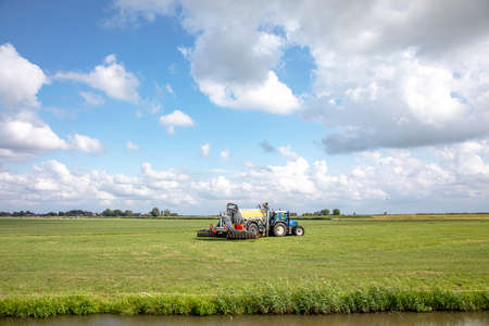 Agricultural tractor drives through a green field under a blue cloudy sky.