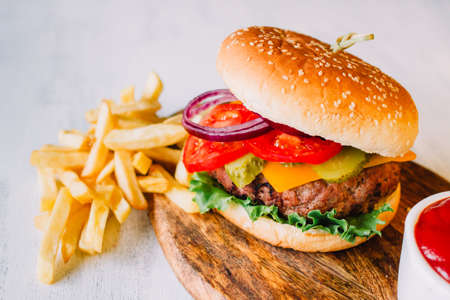 Top view of a big burger on a white background. Typical cuisine from United States of America, representing fast food Banco de Imagens