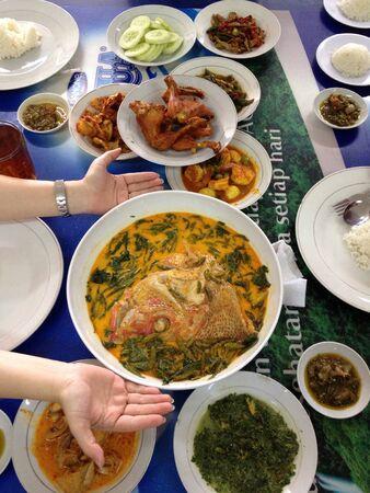padi: Nasi Padang feast with big head curry fish. Stock Photo