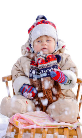 Baby boy on wooden sledge in winter, visible falling snowflakes photo