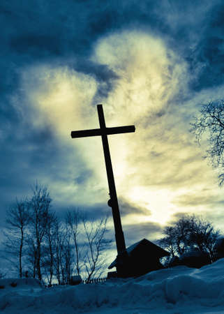 Dramatic scene of deep blue  heart light shining down behind Jesus cross photo