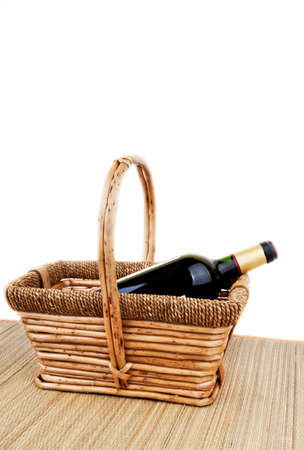 picnic basket with bottle of red dry botlle wine isolated on white photo
