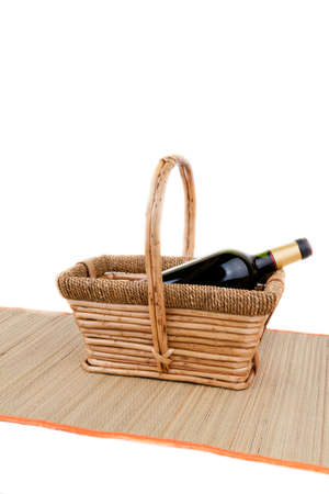 picnic basket with bottle of red dry wine isolated on white photo