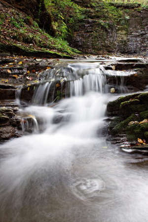 small waterfall on rocks in forest Stock Photo