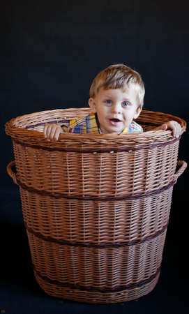 Baby boy sitting in basket, studio shot over black background