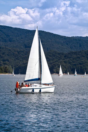 Sailboat at lake over forest hill